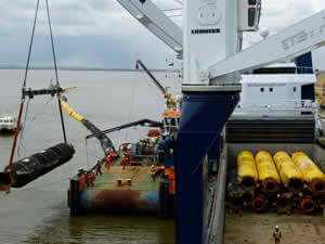 The mv Atlantic unloading floating pipes for a dredging project.