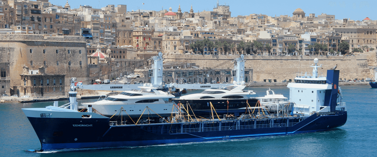 The mv Eendracht with a deck full of yachts with the port historic of Malta on the background.